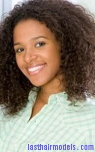 Young woman standing in open doorway, smiling, portrait